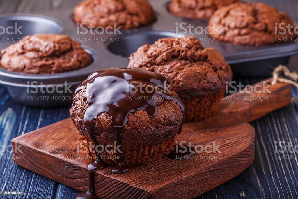 Chocolate muffins with chocolate syrup on dark background. stock photo