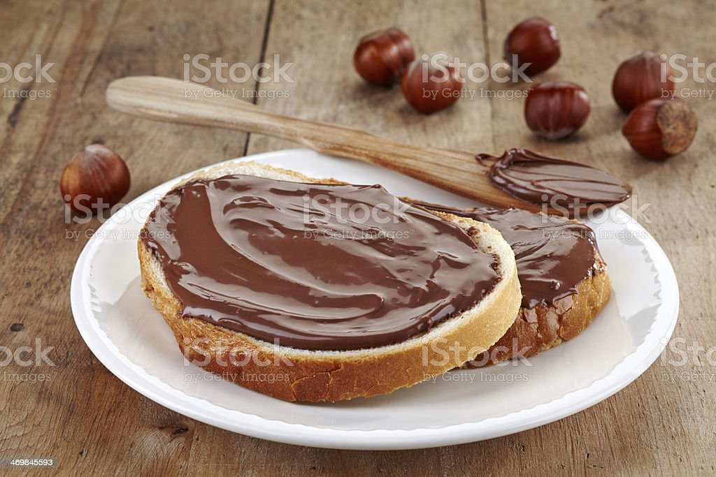 Chocolate nut spread on bread on white plate next to nuts stock photo