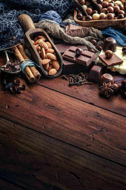 Chocolate, nuts and ingredients in old-fashioned style on wood table stock photo