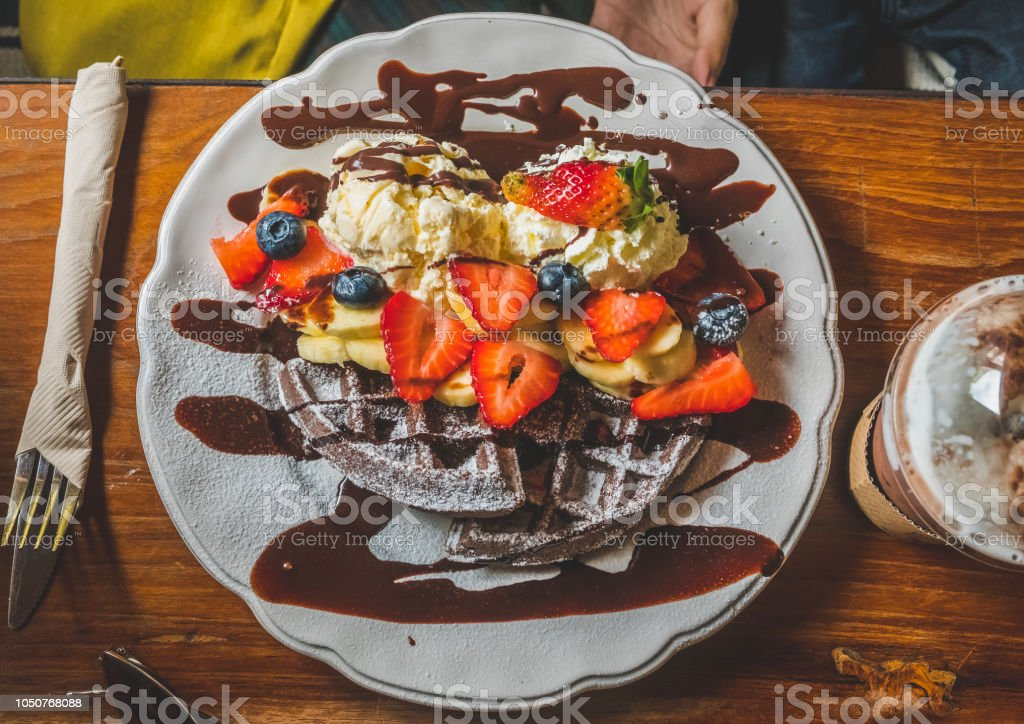 Chocolate Pancakes With Banana Strawberry Blueberry Whipping Cream And Vanilla Ice Cream Icing Sugar Brownies And Chocolate Sauce On Wooden Table Stock Photo Download Image Now Istock