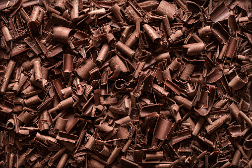 Chocolate pieces background. Top view of chocolate shavings