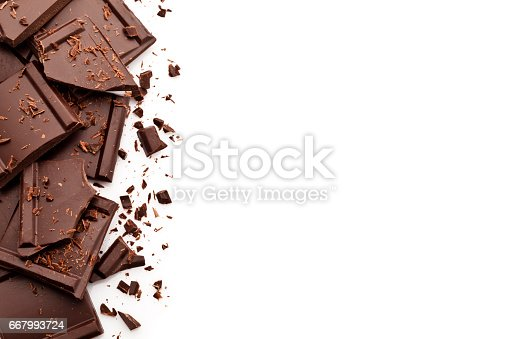 Top view of chocolate pieces placed at the left of an horizontal white background leaving a useful copy space for text and/or logo at the center-right of the frame. Some chocolate shavings are sparse in the composition. Predominant colors are brown and white. DSRL high key studio photo taken with Canon EOS 5D Mk II and Canon EF 100mm f/2.8L Macro IS USM