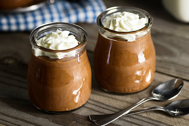Chocolate Pudding with Whipped Cream in Glass Cups Homemade chocolate pudding topped with whipped cream in little glass cups on a wooden table. Two spoons are in the foreground. hauts de france stock pictures, royalty-free photos & images