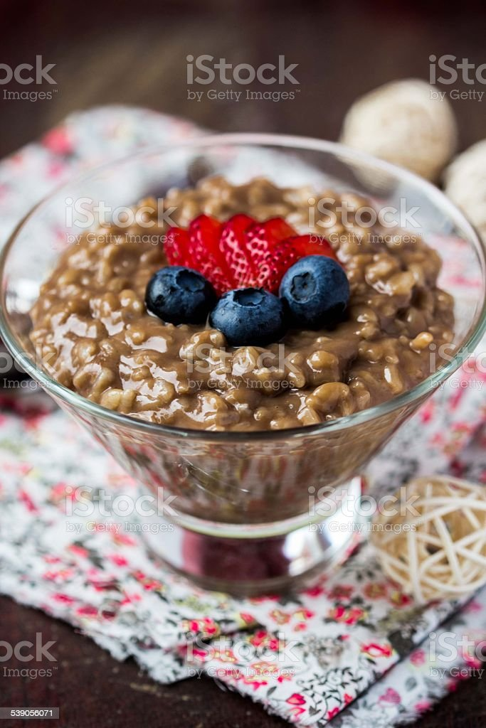 Chocolate rice pudding with strawberries, bilberries, blueberrie stock photo