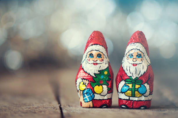 Chocolate Santa Claus with a bag on a old wooden background stock photo