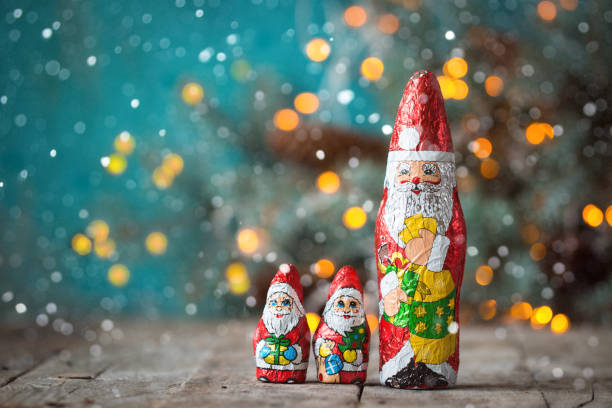Chocolate Santa Claus with christmas lights on a old wooden background. christmas concept stock photo