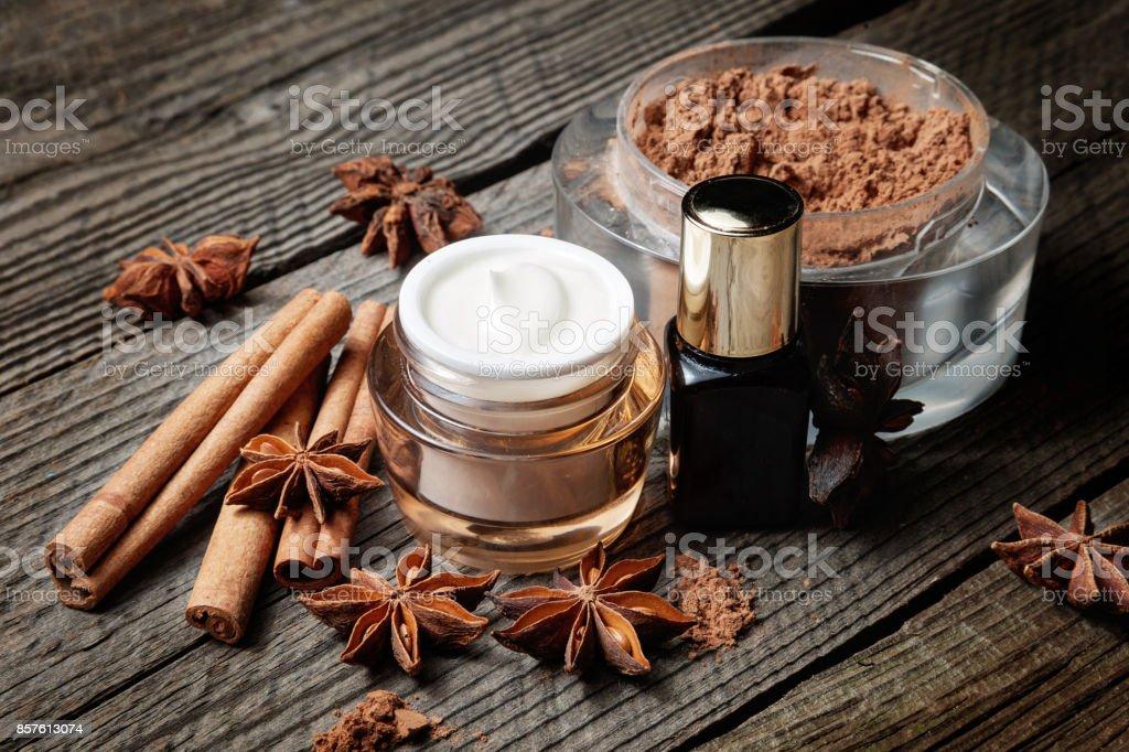 Schokolade Hautbehandlung. Kosmetischer Behälter mit Kakao, Lotion und Serum, Zimtstangen, Anis. – Foto