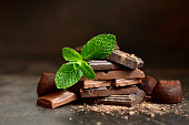 Chocolate slices with fresh mint leaves on a dark slate, stone or concrete background.