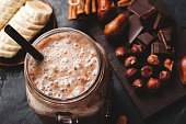 istock Chocolate smoothie in a jar, protein milkshake, nuts, chocolate cubes, banana slices, dates, cinnamon sticks, healthy eating on a dark background 1127304475