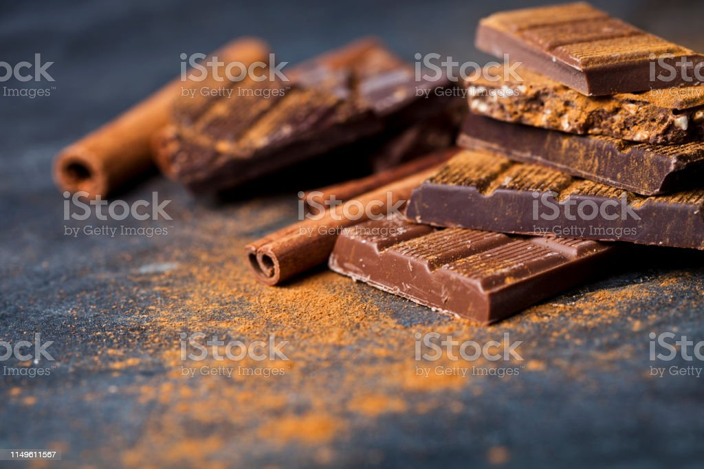 Chocolate stacked on black background. Chocolate bar pieces heap witn...