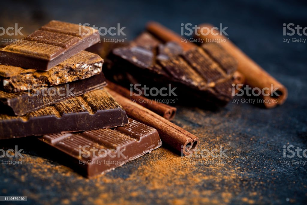 Chocolate stacked on black background. Chocolate bars pieces heap...