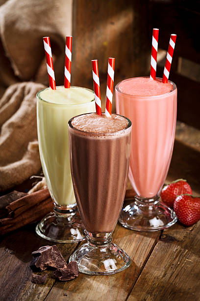 chocolate, strawberry and vanilla milshakes in rustic wood table - milkshake stockfoto's en -beelden