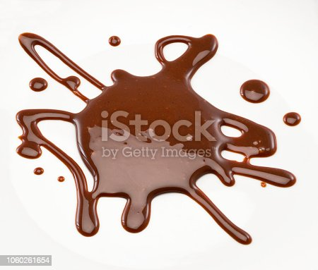 Chocolate syrup poured on a white surface. Studio photography. Cut out. High angle view. Indoors. Copy space.