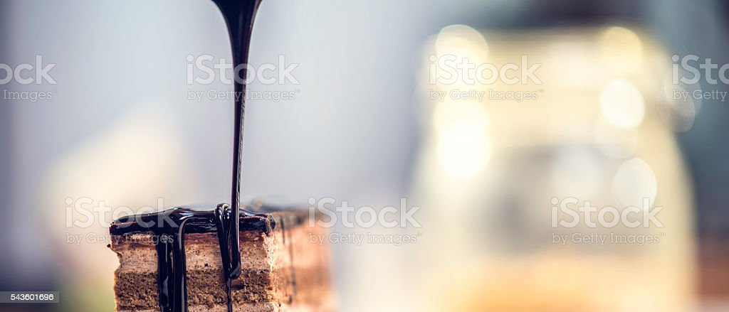 Chocolate syrup pouring on cake stock photo
