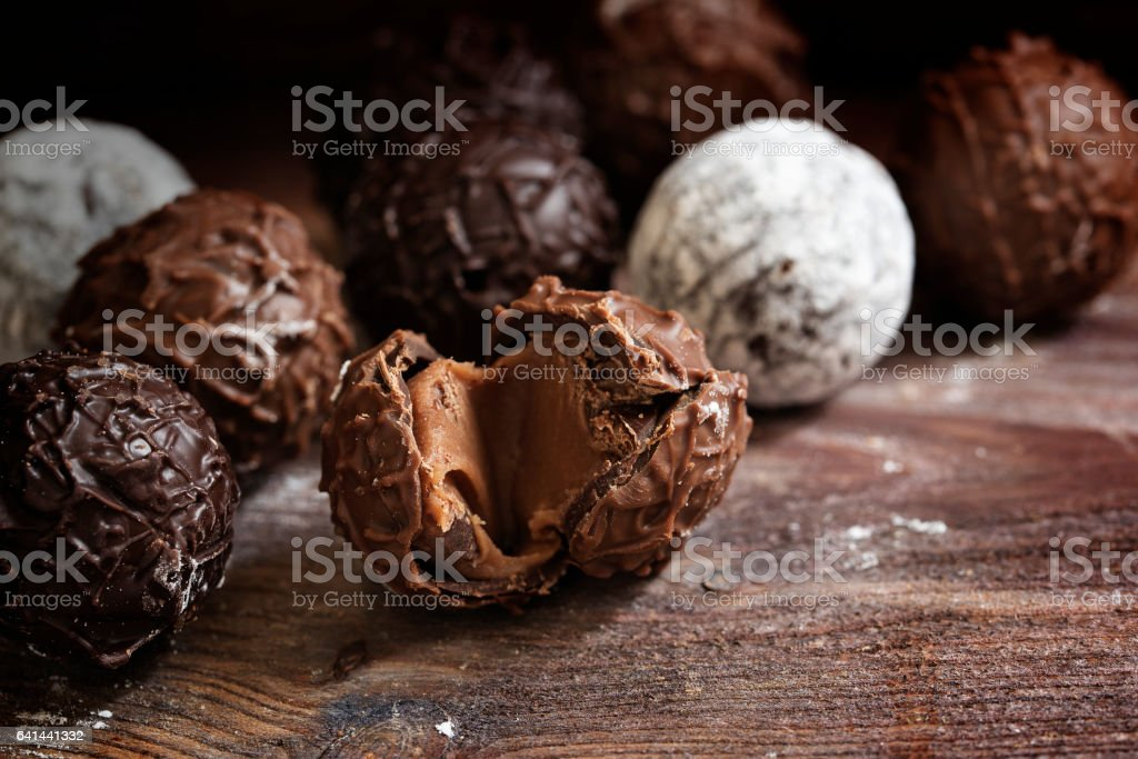 Chocolate truffle pralines on dark rustic wood, close up stock photo