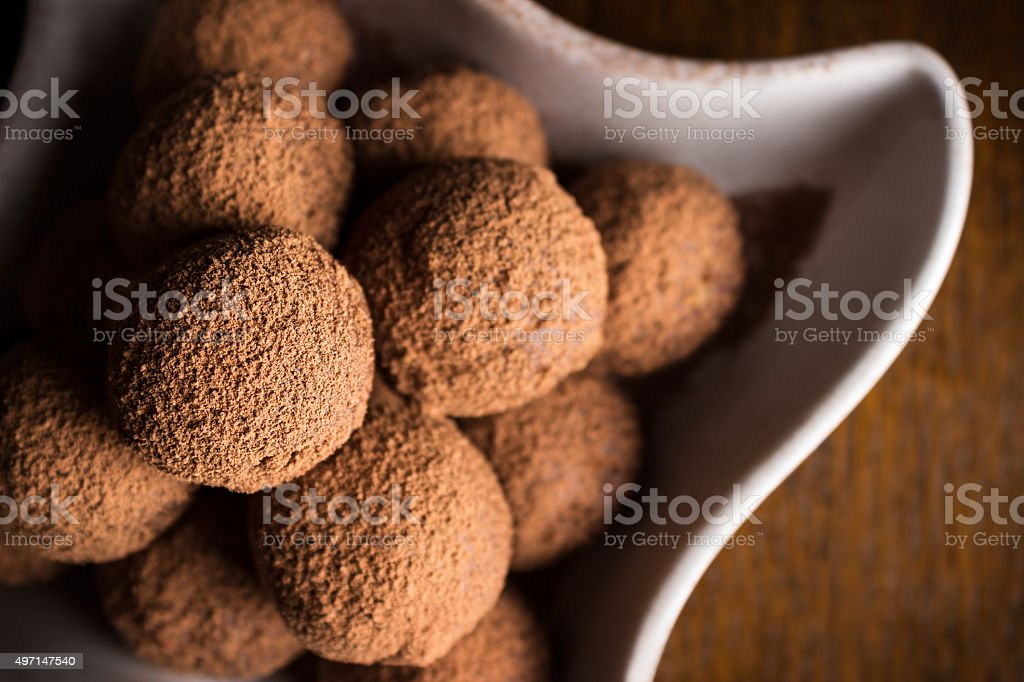 Chocolate truffles in bowl on dark wooden table stock photo