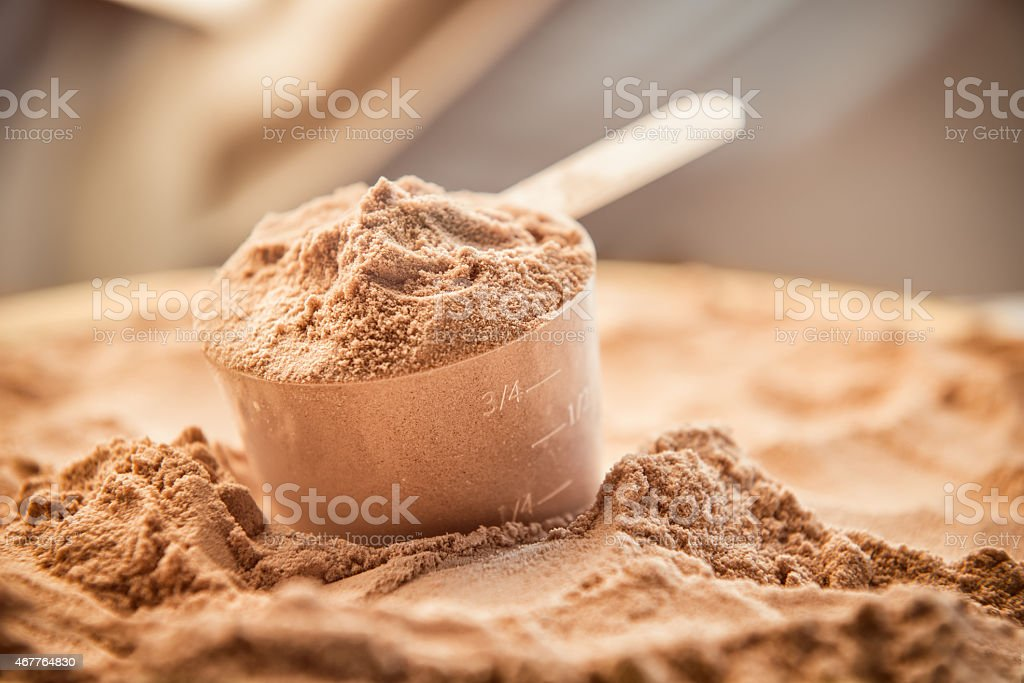 Chocolate whey protein powder with a filled scoop stock photo