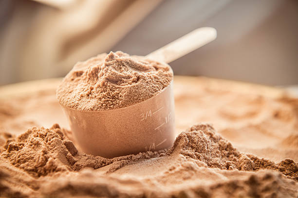 chocolate whey protein powder with a filled scoop - protein stock photos and pictures