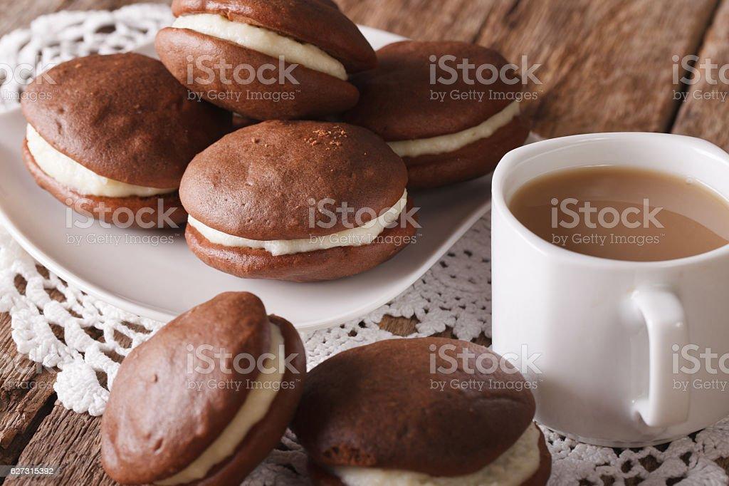 Chocolate Whoopie pie and coffee with milk close-up. horizontal stock photo