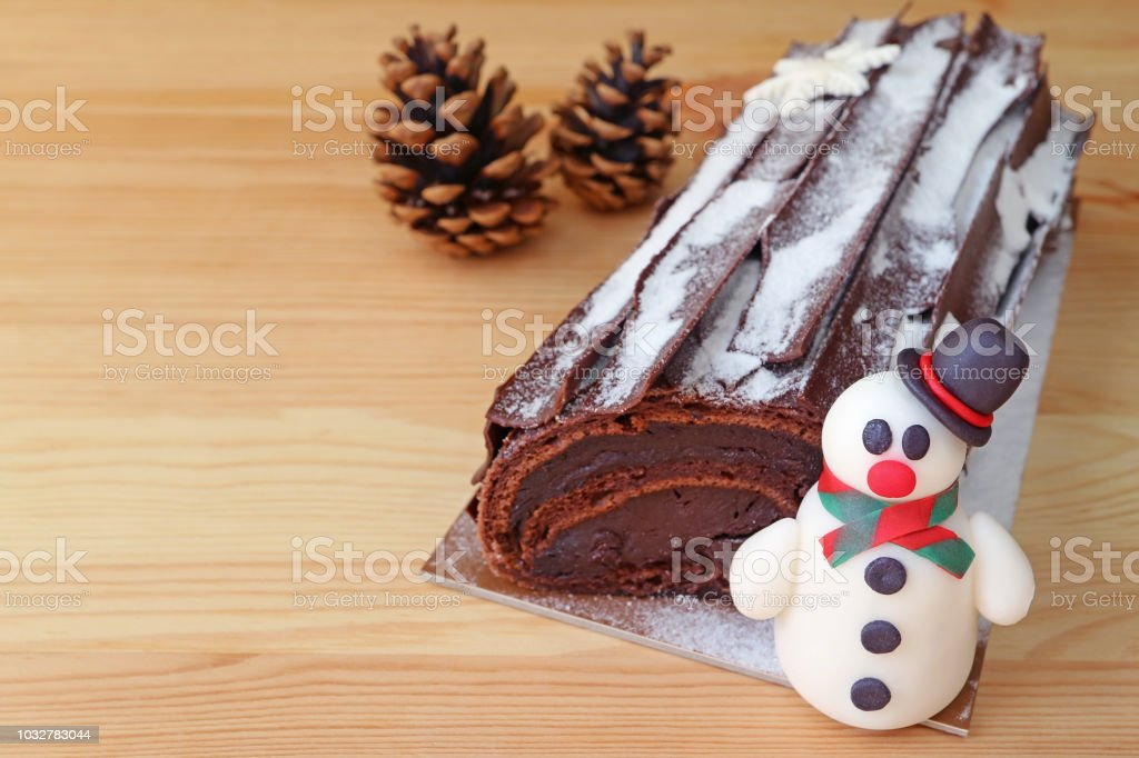 Christmas Yule Log Cake.Chocolate Yule Log Cake For Christmas Or Buche De Noel With A Cute Snowman Marzipan And Two Dry Pin Cones On Light Brown Wooden Table Stock Photo
