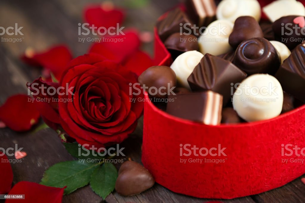 Chocolates in heart shaped box and red roses background- Mother's Day stock photo