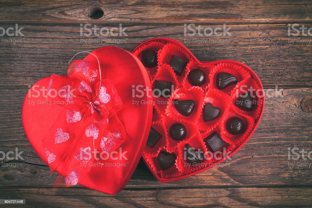Chocolates in red heart box on rustic wooden table stock photo