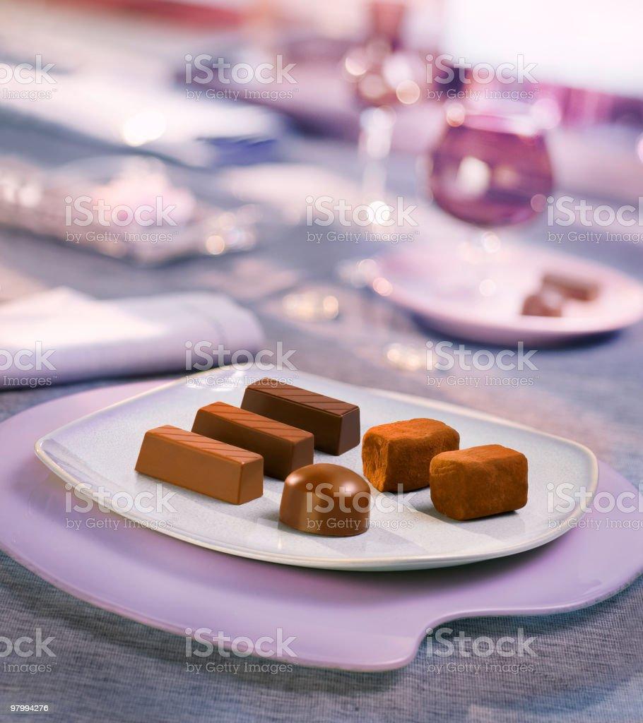 Chocolates on elegant white plate on charming set table royalty free stockfoto