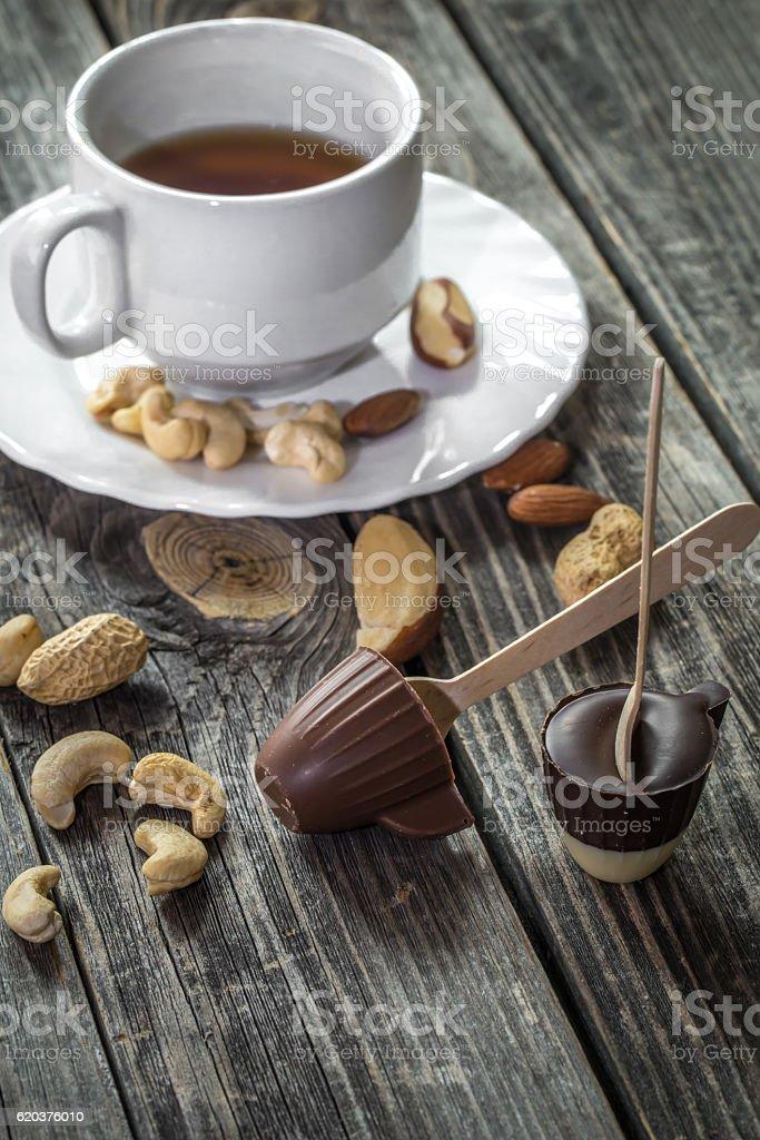 chocolates with tea and nuts on wooden background zbiór zdjęć royalty-free