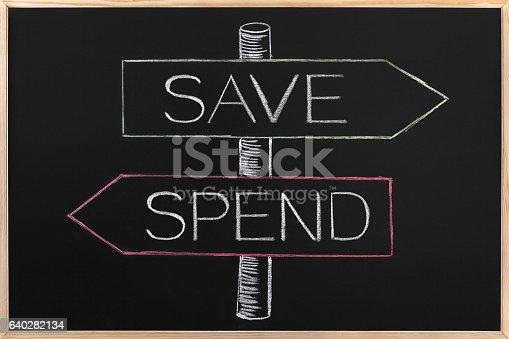 istock Choicе Save or Spend wrriten on opposite arrows on Blackboard 640282134