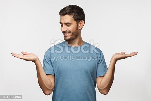 istock Choice concept. Portrait of young man choosing between 2 different options, holding two hands with empty space, isolated on gray background 1041100896