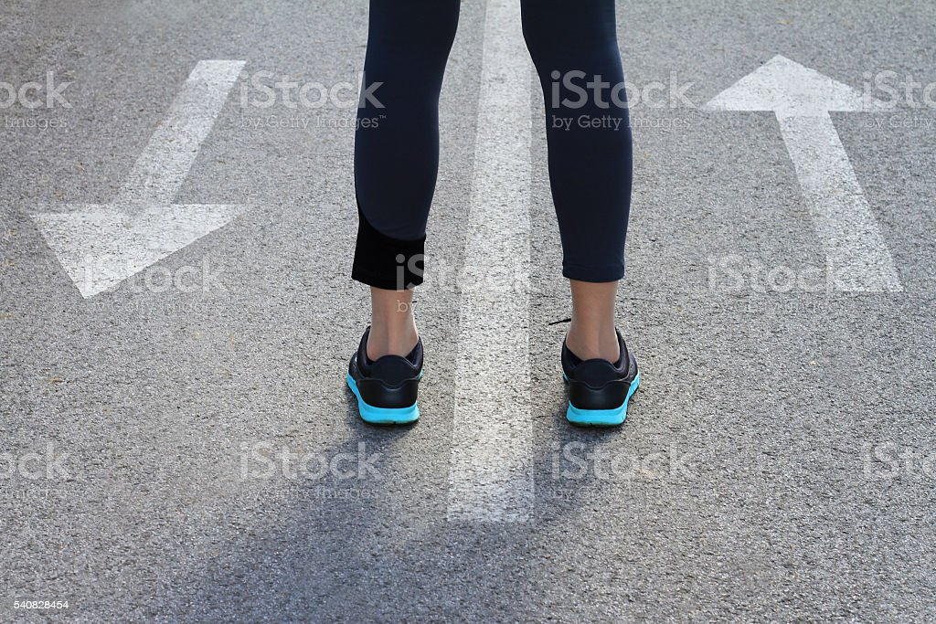 Choice concept. Woman standing between arrows showing different directions. stock photo