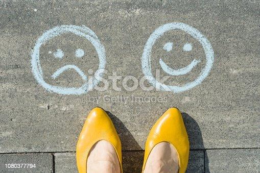 istock Choice - Happy Smileys or Unhappy, text on asphalt road 1080377794