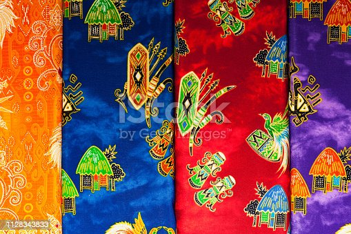 These are low priced fabrics at a traditional Indonesian textile market in Sorong.  In the social and religious lives of Indonesians textiles are very important.  The symbolism of the various ethnic groups is evident in the variety of textiles.  Color, shapes and their arrangements all have special meanings. Certain designs can only be worn by women or men, or only by the members of the royal family or nobility. Special textiles are worn or exchanged in life cycle or rights of passage ceremonies celebrating birth, circumcision, puberty, marriage, childbearing and death.  Textiles play an important role in many traditional events and ceremonies.  Among non oil or gas industries the textile and apparel industry is the largest export earner.  Sorong, West Papua, Indonesia  0°53'16.059