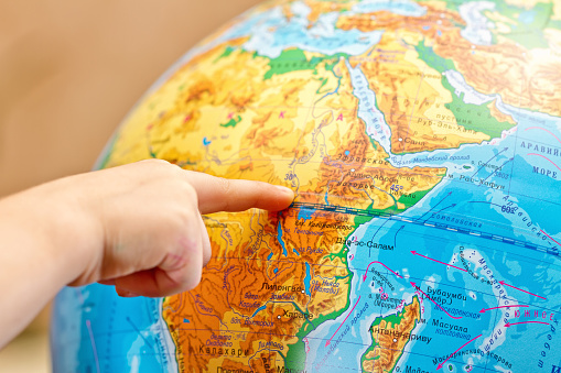 girl points to a location in Africa on the globe