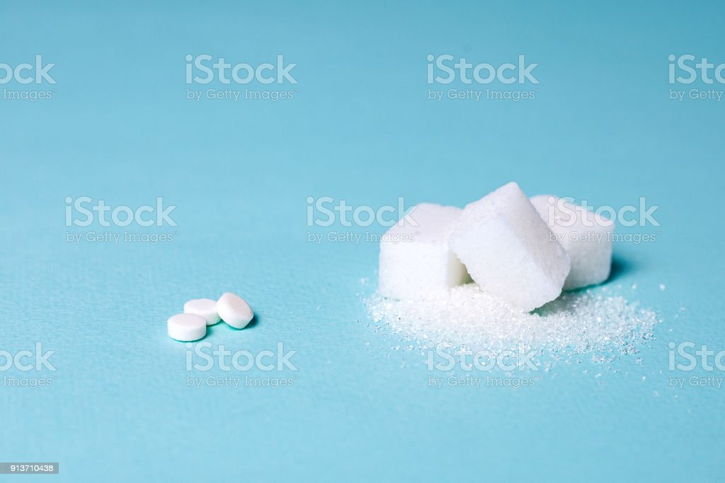 Choice of Sweetener in tablets or regular sugar. Alternative to sugar for people with diabetes. On a green background white sugar in cubes and sugar substitute in tablets stock photo