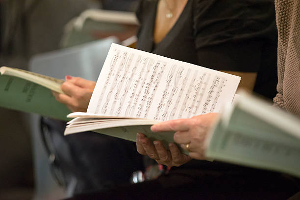 Choir singers holding musical score Choir singers female hands holding musical scores sheet music stock pictures, royalty-free photos & images