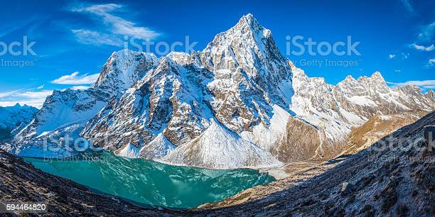 The snowy ridges and icy summit of Cholatse (6440m) soaring over the dramatic north face reflecting in the turquoise waters of the glacial lake below, deep in the remote Himalaya mountain wilderness of the Everest National Park, a UNESCO World Heritage Site, Nepal.