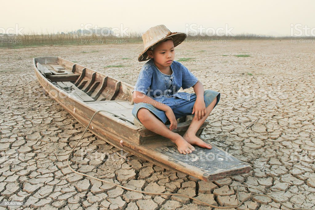 Choldren and wooden boat on cracked earth stock photo