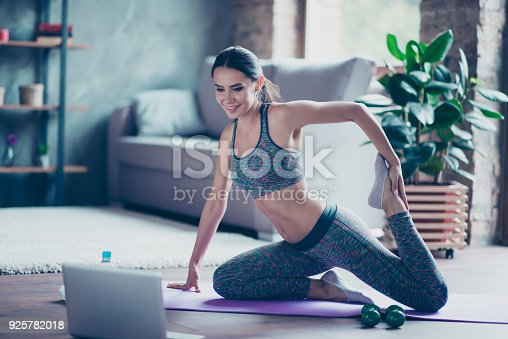 istock I choose healthy and sportive lifestyle! Pretty beautiful woman is stretching her legs, feet and doing exercise at home on the floor, she is watching helpful videos on the internet 925782018