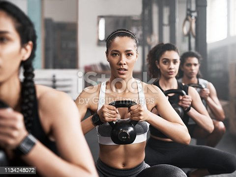 Shot of a group of fit young women working out with kettle bells at the gym