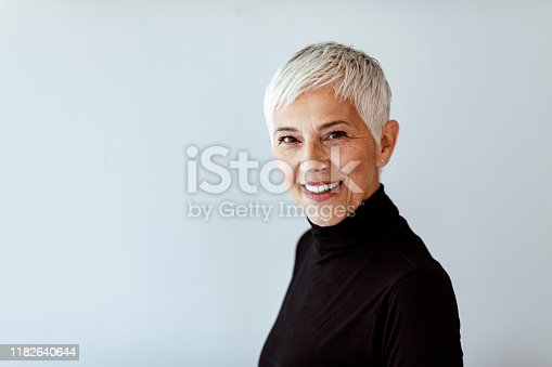 Portrait of beautiful senior woman with white hair looking at the camera wearing black turtleneck. Close up facial portrait of a beautiful senior woman looking at the camera with a warm friendly smile and attentive expression