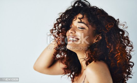 Cropped shot of an attractive young woman feeling playful while posing against a gray background in the studio alone