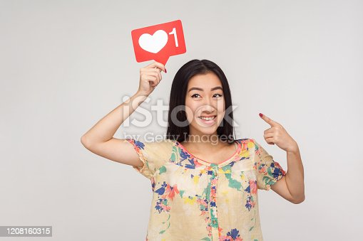 640248524 istock photo Choose trendy social media content! Happy enthusiastic asian girl in blouse pointing at heart icon over her head 1208160315