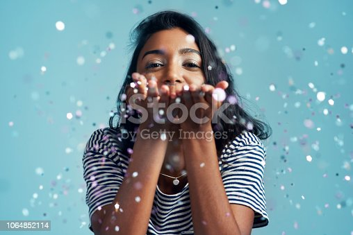 Cropped shot of a beautiful young woman blowing confetti in the studio