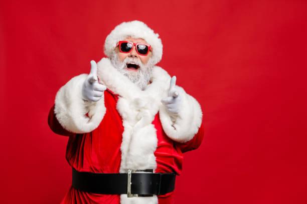 Choose winter season sales. Close up photo of cool stylish trendy santa indicate discount shopping bargain wear eyeglasses eyewear cap hat isolated over red background stock photo