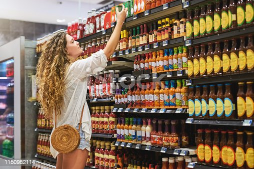 Shot of a beautiful young woman doing some shopping at a grocery store