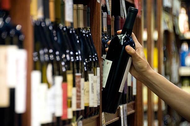 escolher uma garrafa de vinho - prateleira compras imagens e fotografias de stock