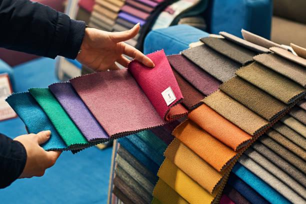 choosing a fabric color in a store - przemysł włókienniczy zdjęcia i obrazy z banku zdjęć
