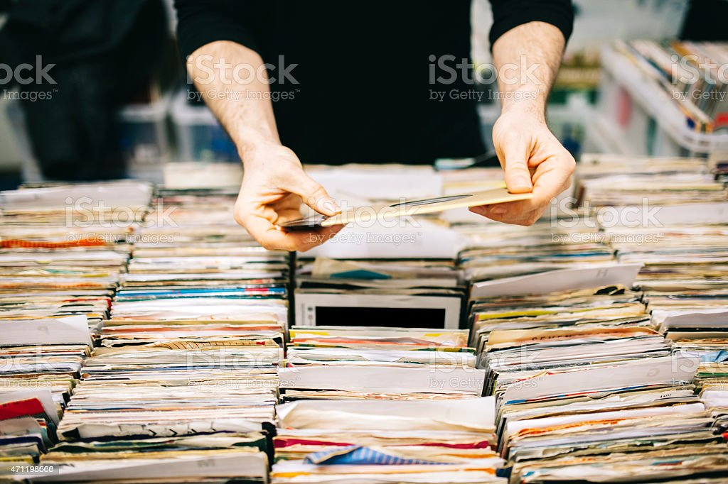 Choosing a second hand vinyl record in a record store stock photo