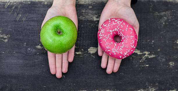 Choosing between apple and doughnut Choosing between apple and doughnut unhealthy eating stock pictures, royalty-free photos & images